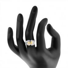 Prstan srebrne barve, upognjena konca krakov, bleščeči prozorni in barvni cirkoni